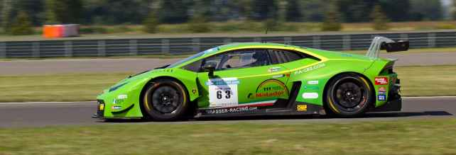 green sports car on gray asphalt road